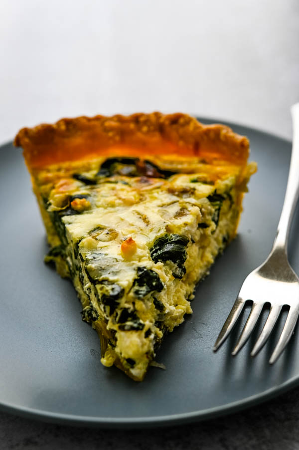 a slice of florentine quiche on a plate.