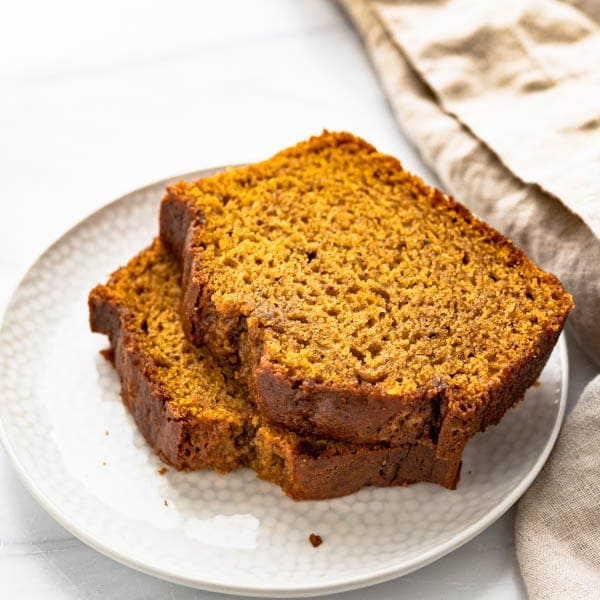 Moist pumpkin bread sliced on a plate.