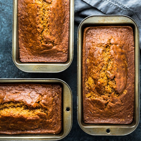 3 loaves of spiced pumpkin bread in loaf pans.