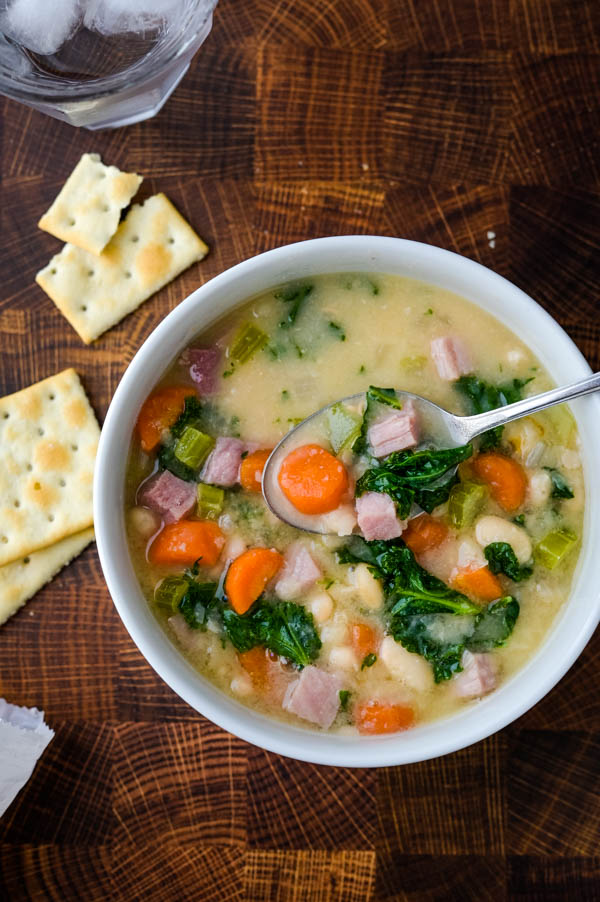 Dishing up a spoonful of hearty soup with saltine crackers on the side.