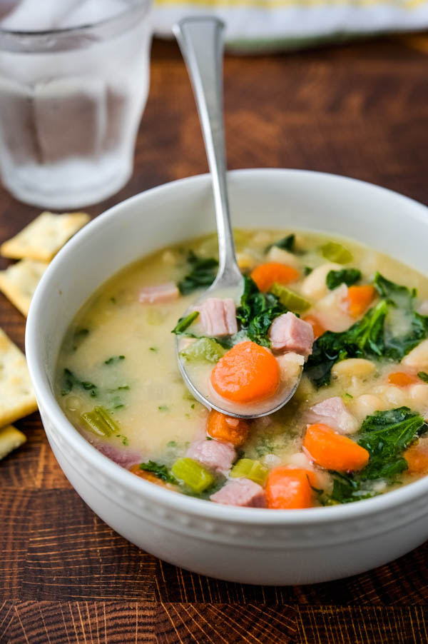 A bowl of ham hock and bean soup with vegetables and kale.
