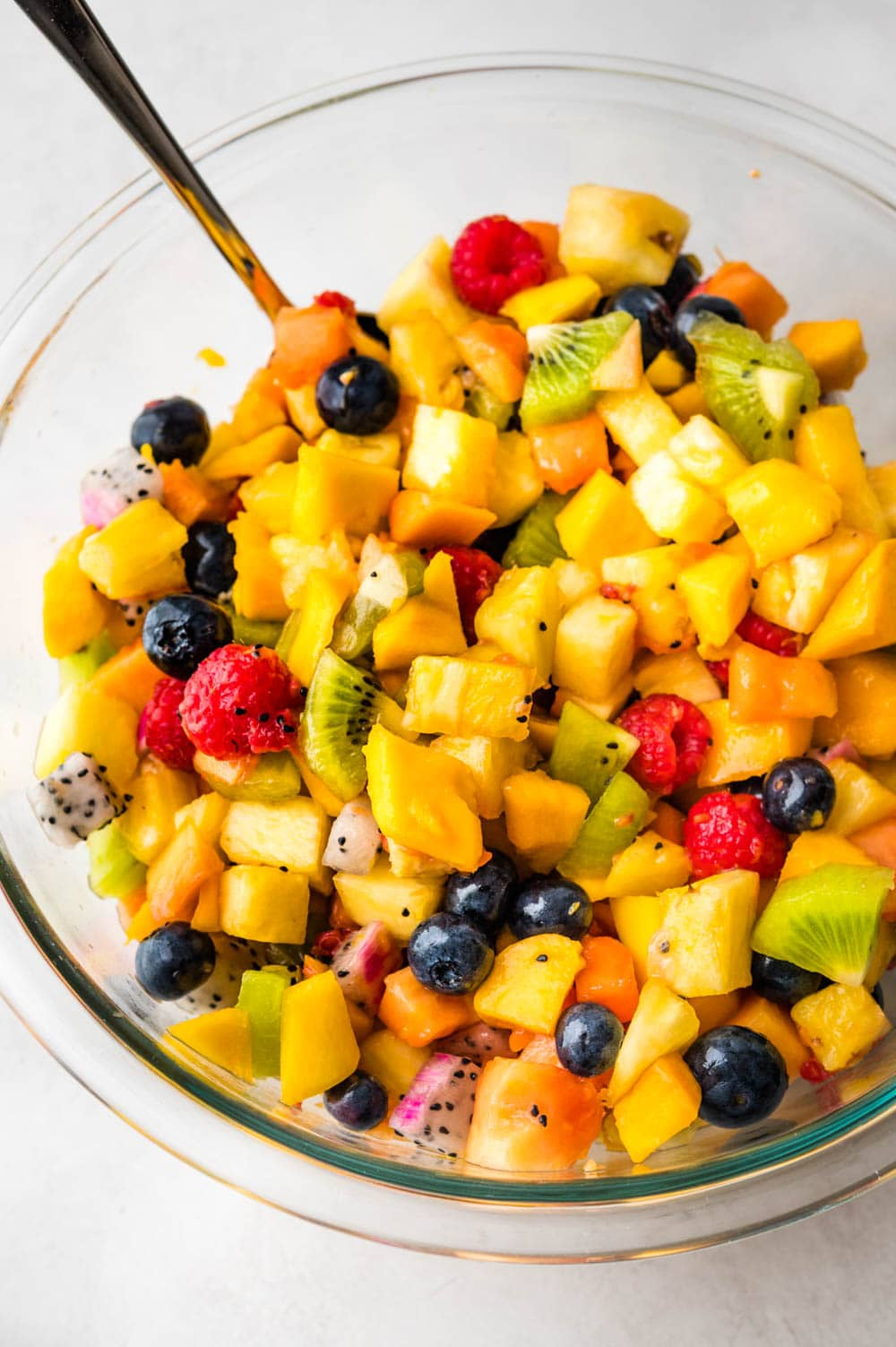 a bowl of tropical fruit salad with honey lime dressing and exotic fruits.