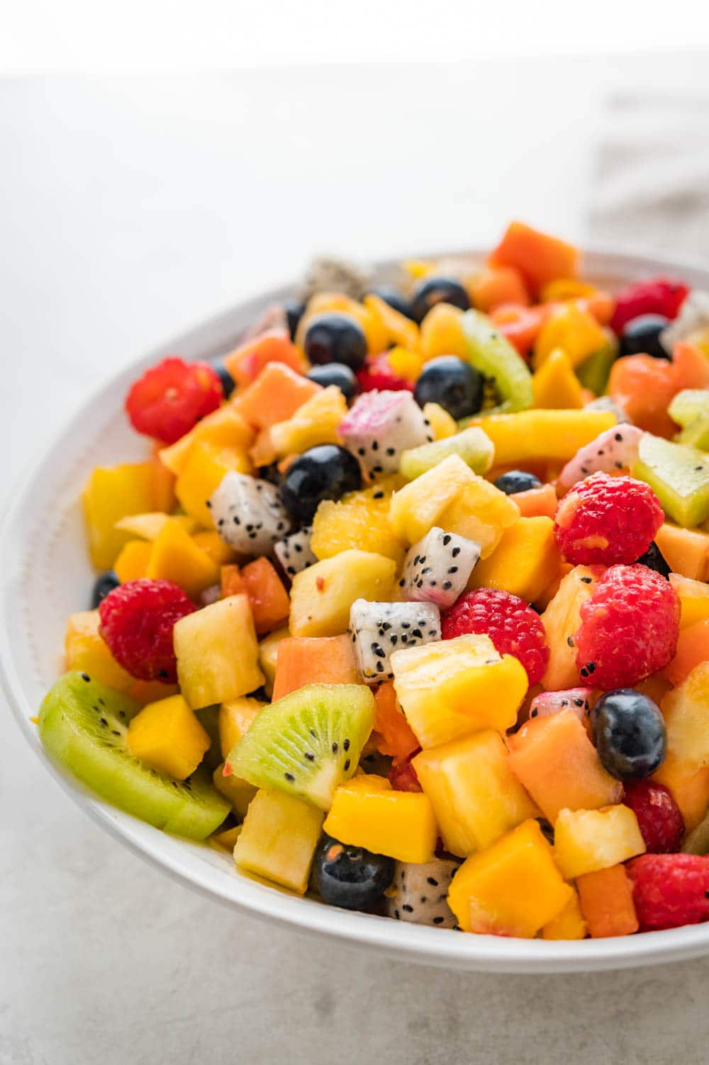 a bowl of fresh fruit salad with honey lime dressing.