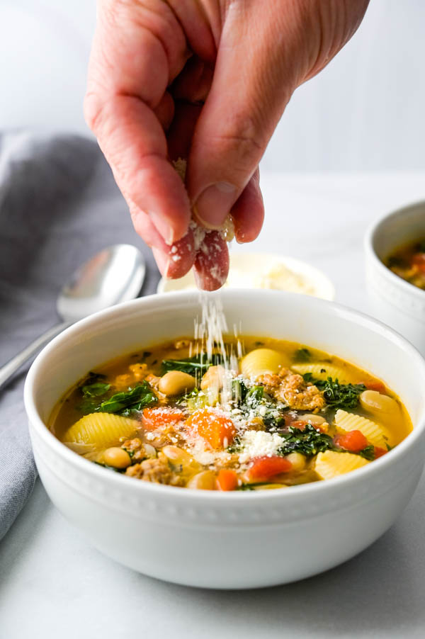 Sprinkling parmesan cheese over a bowl of Tuscan Sausage Soup.