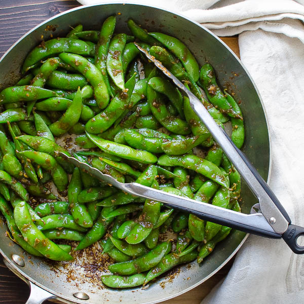 tossing edamame with tongs