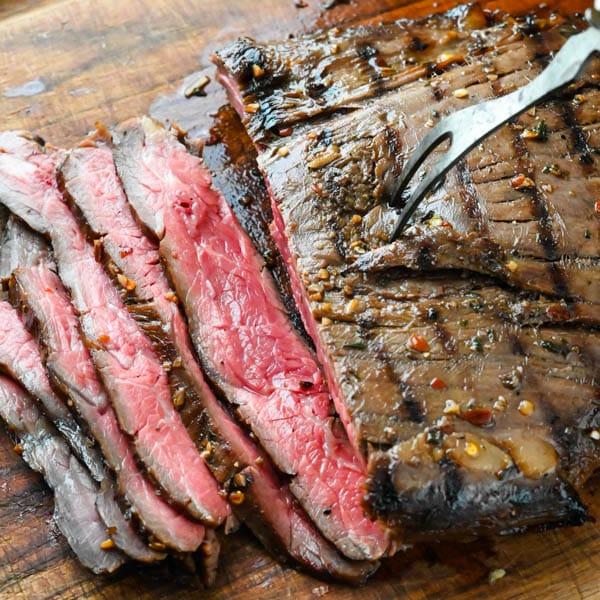 Slicing flank steak on a cutting board.