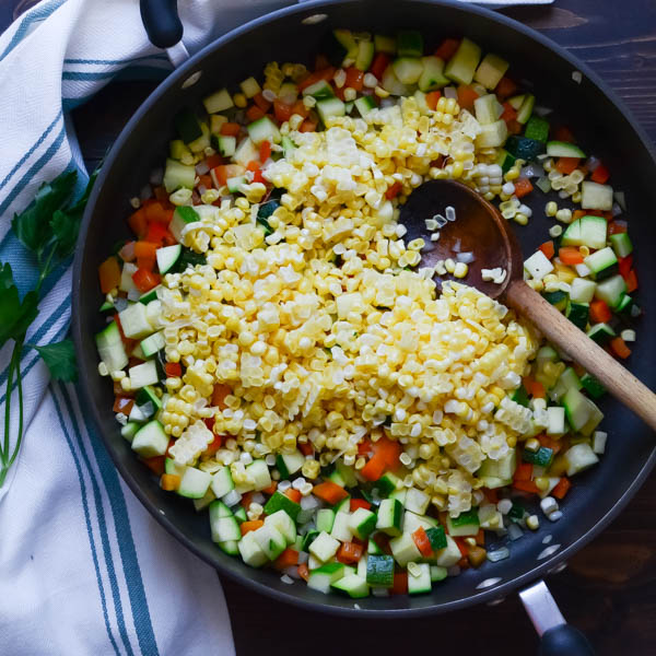 chopped vegetables in a pan with wooden spoon.