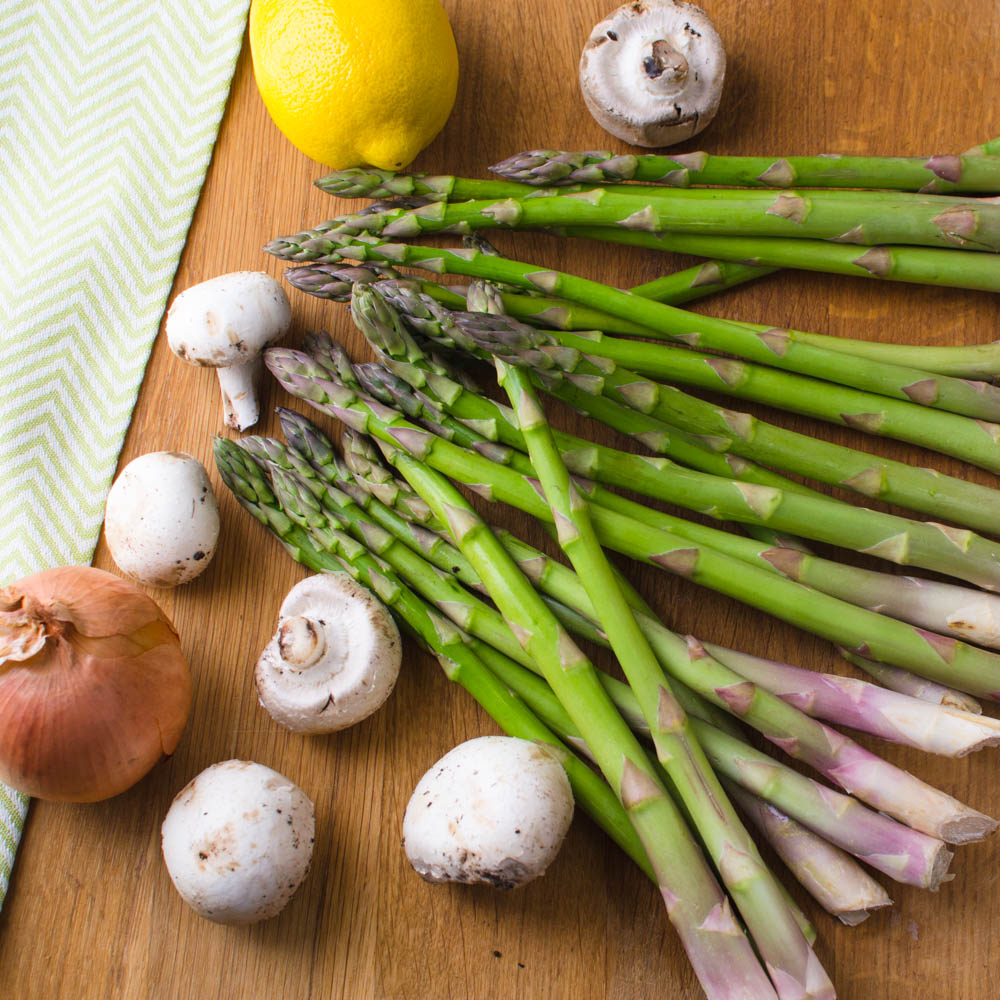 Mushrooms asparagus onion and lemons on a cutting board for healthy pasta primavera.