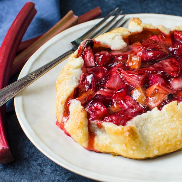 strawberry rhubarb galette with homemade pastry with a fork.