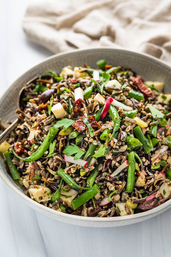 Italian Wild Rice salad with Sherry Shallot Vinaigrette in a serving bowl.