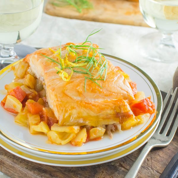 plank grilled salmon with tomato fennel ragout with a fork and glass of wine.