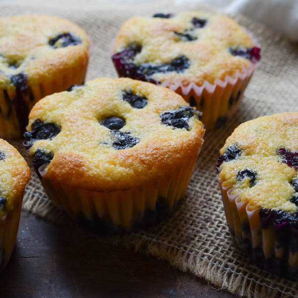Lemon Blueberry Corn Muffins in paper cups.