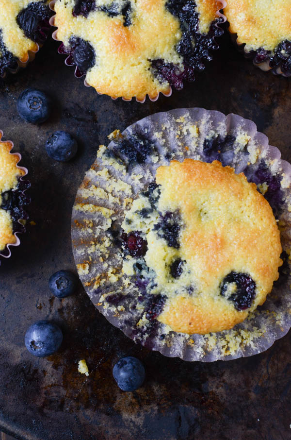 Lemon Blueberry Corn Muffins with paper liner pulled back.
