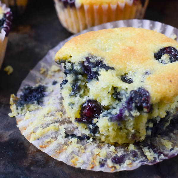 closeup of Lemon Blueberry Corn Muffins with a bite removed.