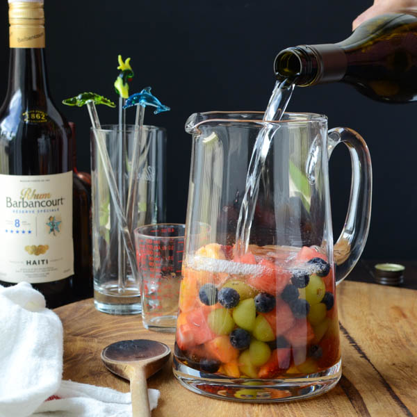 pouring wine into a pitcher with fruit.