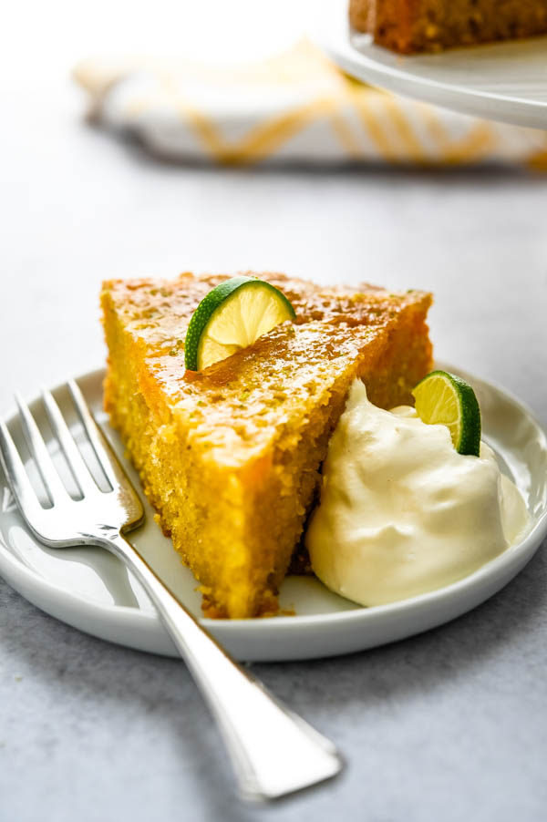 Serving mango cake recipe on a plate with a fork and garnish.