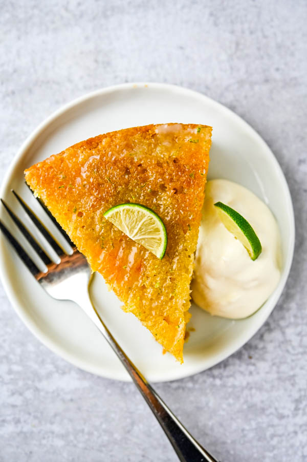 A slice of the mango dessert on a plate with lime and whipped cream. The confectioners glaze adds a shine.