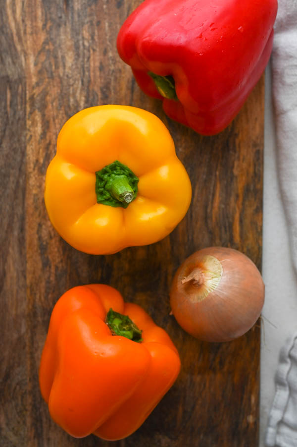 red, yellow and orange bell peppers with an onion.