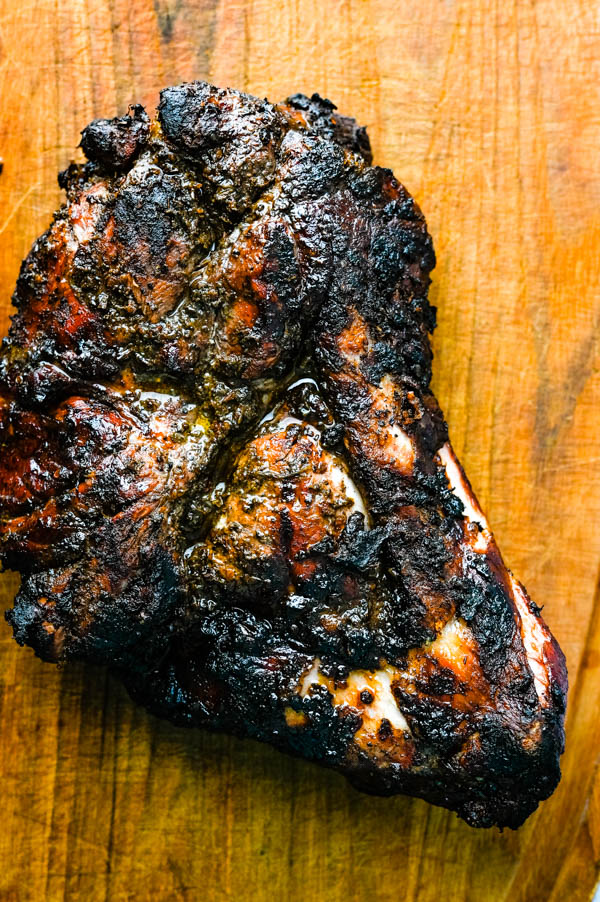 jerk pork recipe after smoking and grilling on a cutting board to rest.