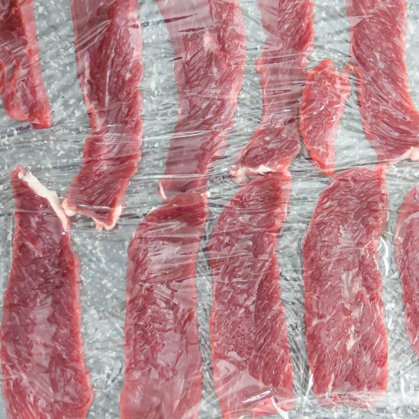 thinly sliced beef in plastic wrap