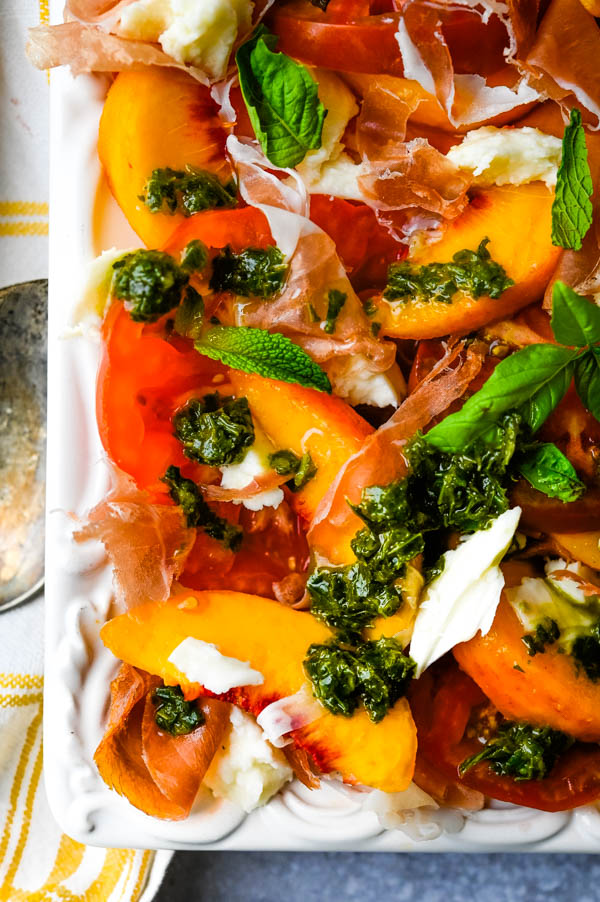drizzling basil herb sauce over tomato peach salad.