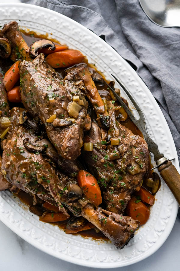 a platter of slow cooked lamb shanks with vegetables and gravy.