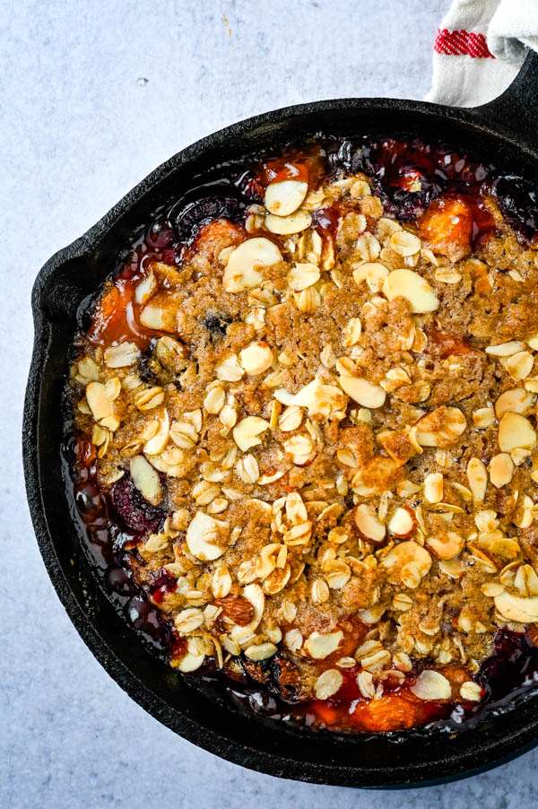 Baked Peach Crisp recipe in a cast iron skillet.