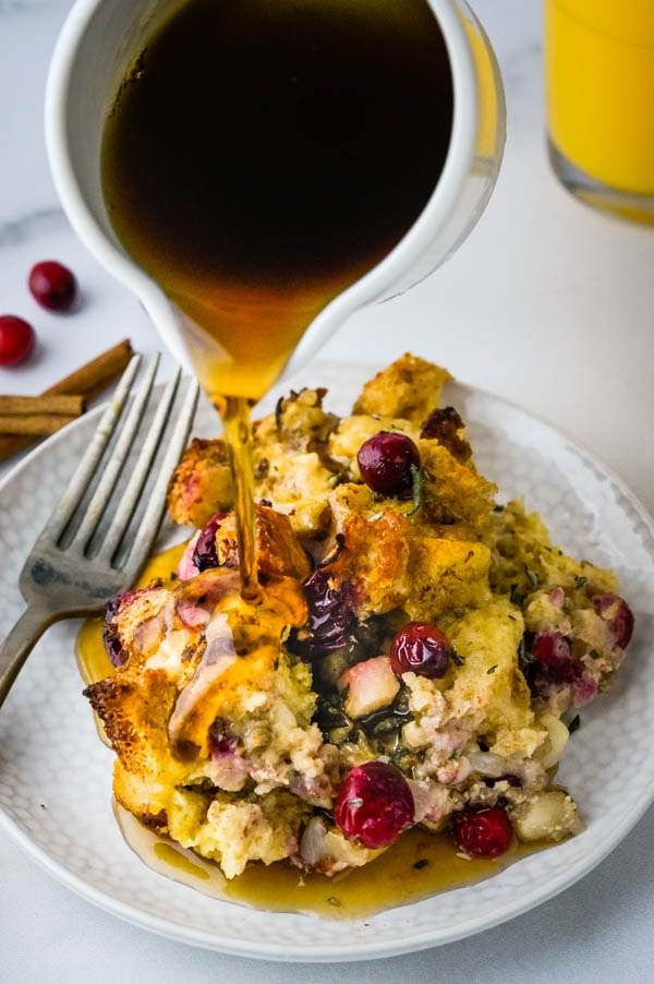 pouring maple syrup over the breakfast casserole.
