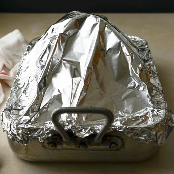 tightly tenting the oven roasted ham with aluminum foil.