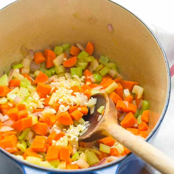 sautéing carrots, onions, celery and garlic in a pot for green pea soup recipe.
