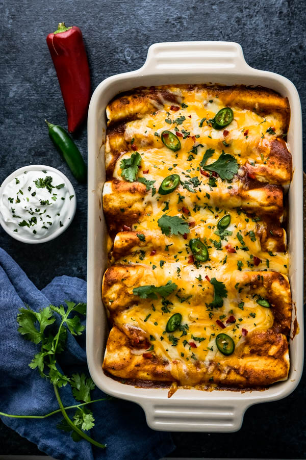 Serving chicken and black bean enchiladas with sour cream, cilantro and sliced chiles.