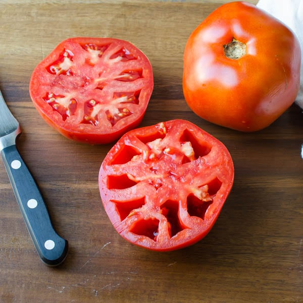 2 ripe tomatoes on a cutting board with a knife, one cut in half and seeded.