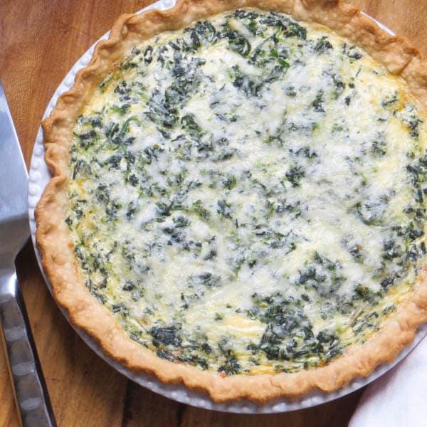 spinach artichoke quiche with a pie server.