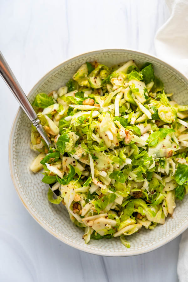 serving shaved brussels sprouts salad in a bowl with serving spoon.