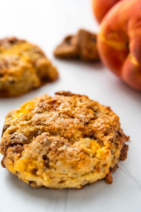 a single butter scone with bits of praline and peaches peaking out.