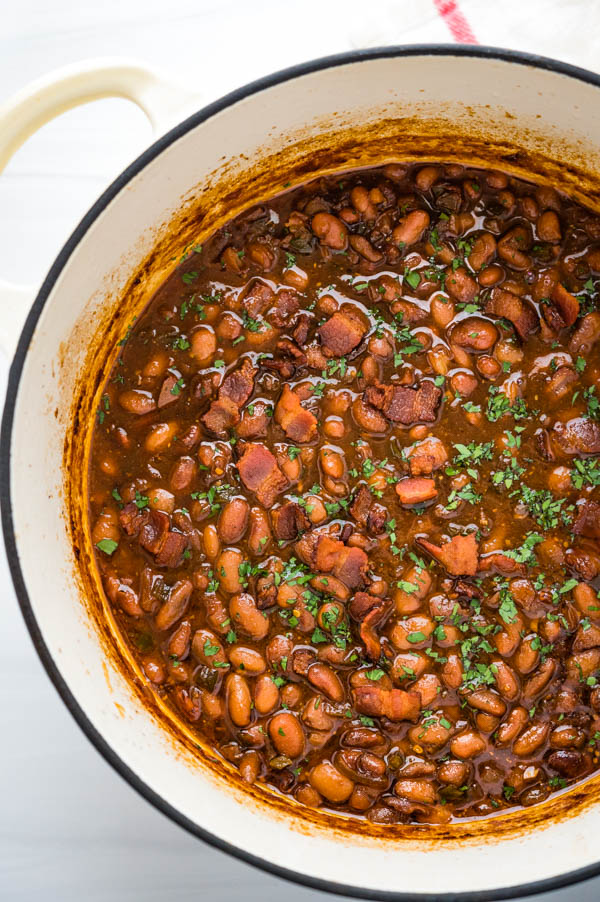 A Dutch oven pot filled with Old fashioned Southern baked beans.