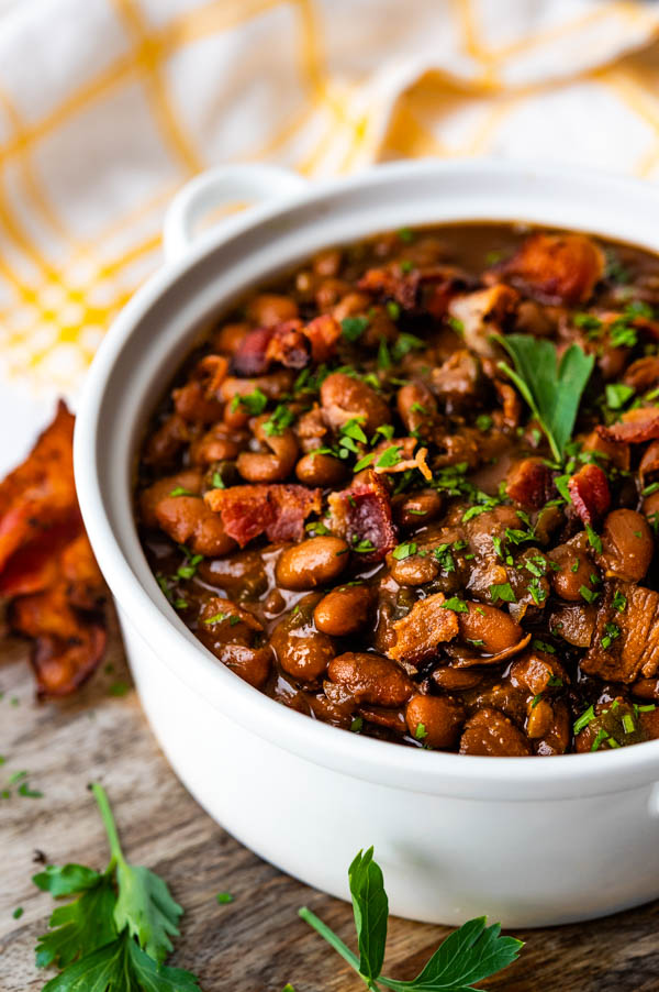 Serving BBQ baked beans with extra bacon and parsley.