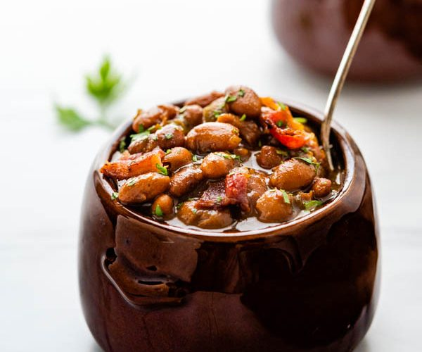 Old fashioned baked beans in a crock with a spoon.
