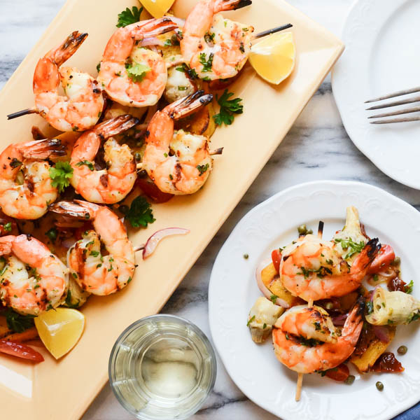 Italian-Style Grilled Shrimp and Polenta on plates with wine.