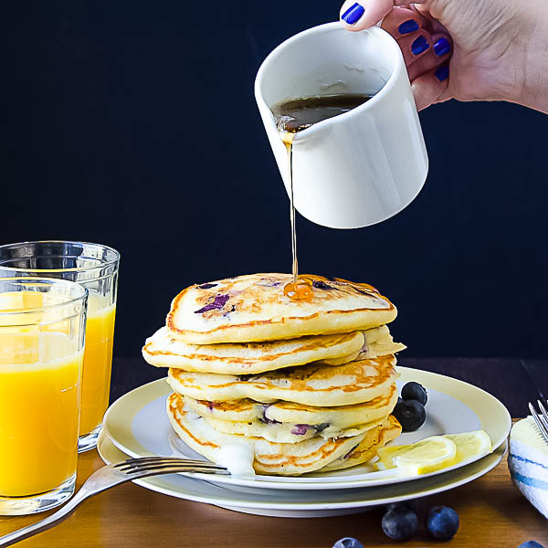pouring syrup on Blueberry Lemon Cornmeal Pancakes