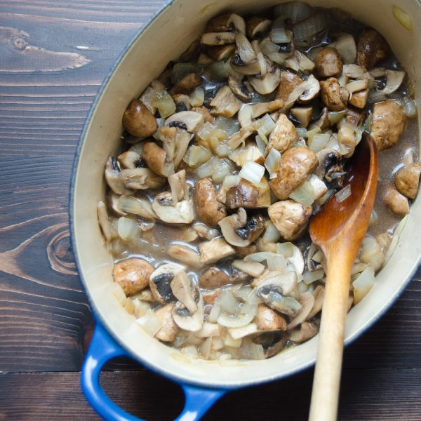mushrooms in a pot with wooden spoon