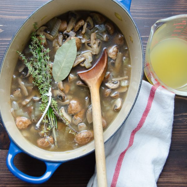 mushrooms broth and herbs with spoon
