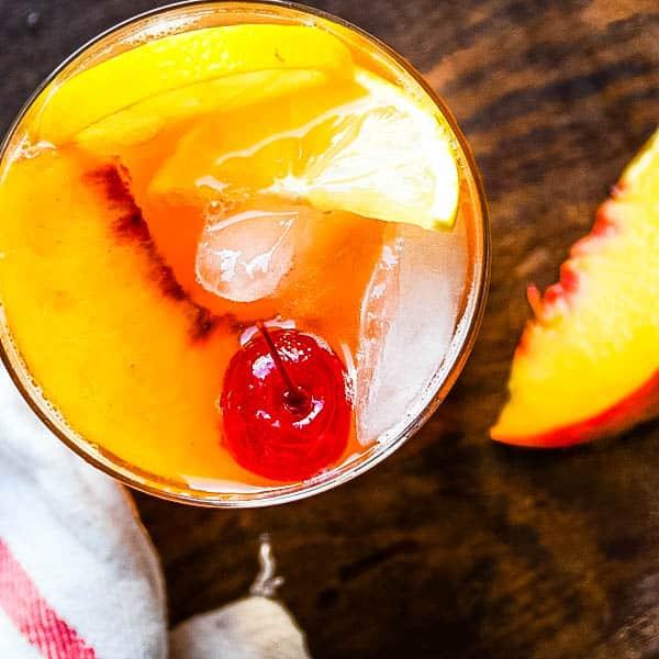 Fresh peach and bourbon sour with a cherry and peach garnish.