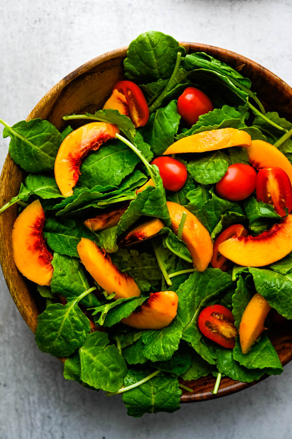 baby kale salad with juicy peach.
