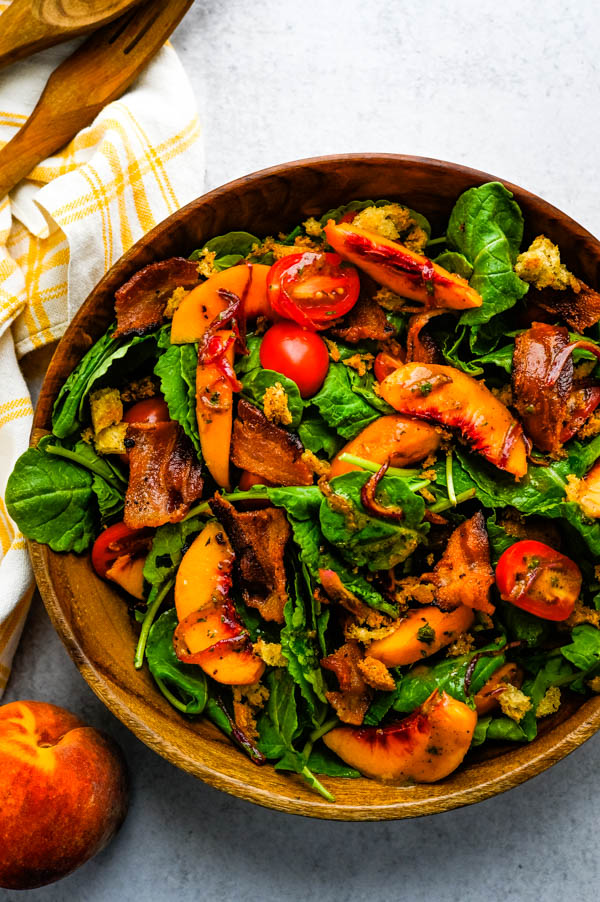 Juicy Peach and Baby Kale Salad with Warm Bacon Dressing in a bowl with serving utensils.