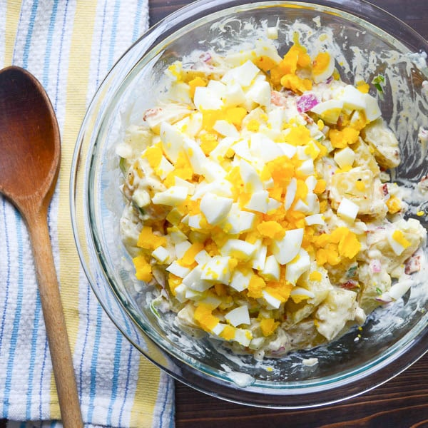 adding chopped egg to potato salad.