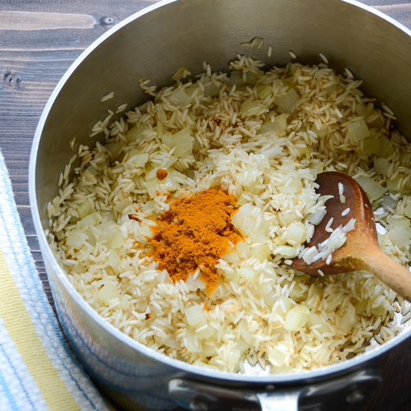 rice, onions and turmeric in a pot with a wooden spoon.