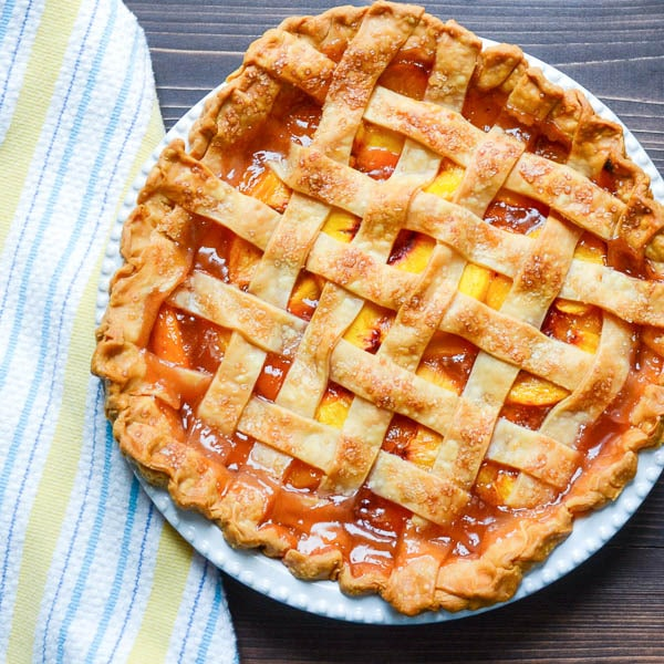 fresh peach pie with lattice crust straight from the oven.
