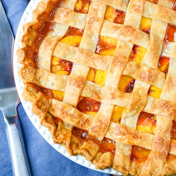 Fresh Peach Pie with Lattice Crust and a server.