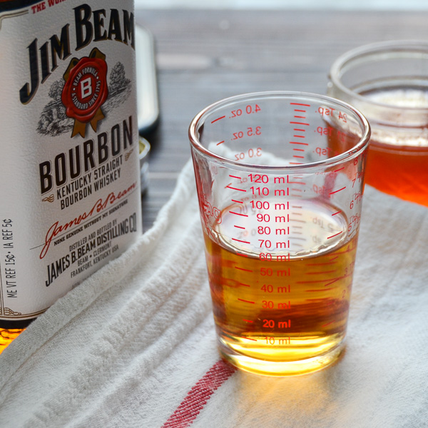 measuring the bourbon in a glass measuring cup for the bourbon sour recipe.
